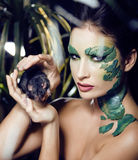 Woman with creative make up like snake and rat in her hands, halloween horror closeup joke scary Royalty Free Stock Image