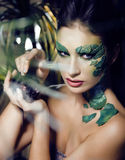 Woman with creative make up like snake and rat in her hands, halloween horror closeup joke scary Stock Photos