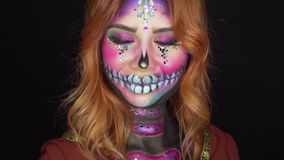 Woman with creative make-up of sugar skull in pink and purple colors and flowers. Positive emotions alive, portrait of girl with creative make-up of sugar skull stock footage