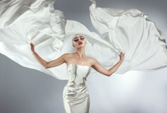 Woman with creative make-up in a white cloth flying. A girl holding a flying white cloth Royalty Free Stock Images