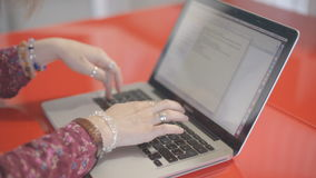 Woman creative profession with rings on hands typing on a laptop keyboard, text document on screen. She sits at a red lacquer table. Her fingers wearing a stock video footage