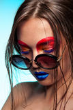 Woman with creative red and blue make up wearing sunglasses Royalty Free Stock Image