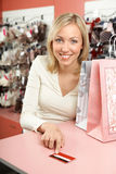 The woman with a credit card. The woman in shop with packages smiles and holds in a hand a credit card Stock Photos