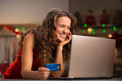 Woman with credit card choosing Christmas gifts on laptop Stock Photography