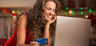 Woman with credit card choosing Christmas gifts on laptop Royalty Free Stock Photo
