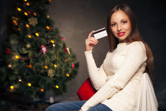 Woman with credit card in front of Christmas tree Stock Photography