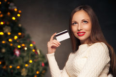 Woman with credit card in front of Christmas tree Royalty Free Stock Photos
