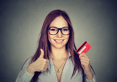 Woman with credit card giving thumbs up hand gesture Royalty Free Stock Image