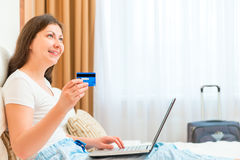 Woman with credit card and laptop dreaming Stock Photos