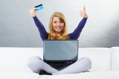 Woman with credit card paying over internet for online shopping, modern technology. Happy woman holding credit card and showing thumbs up, using laptop sitting Royalty Free Stock Images