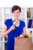 Woman with credit card and shopping bag in the kitchen Stock Images
