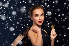 Woman with credit card and shopping bags over snow. People, luxury, christmas, holidays and sale concept - beautiful woman with credit card and shopping bags Royalty Free Stock Image