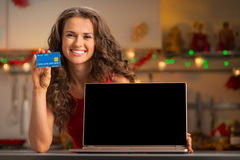 Woman with credit card showing laptop blank screen Stock Photo