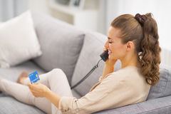 Woman with credit card talking phone while laying on sofa Stock Photo