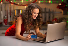 Woman with credit card typing on laptop in Christmas kitchen Royalty Free Stock Photos