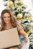 Woman with credit card using laptop near christmas tree Stock Photo