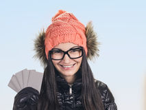 Woman with credit cards. Portrait of young smiling woman holding credit cards like a fan on blue sky background . wearing in winter cap, spectacles , jacket Stock Images