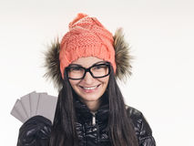 Woman with credit cards. Portrait of young smiling woman holding credit cards like a fan on grey background. wearing in winter cap, spectacles , jacket, black Royalty Free Stock Photos