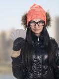 Woman with credit cards. Portrait of young smiling woman holding credit cards like a fan on sunny city background. wearing in winter cap, spectacles , jacket Royalty Free Stock Photo