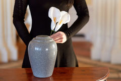 Woman with cremation urn at funeral in church. Cremation, people and mourning concept - woman with flowers and cinerary urn at funeral in church stock photos