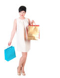 Woman in creme dress with shopping bags posing Stock Image