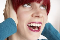 Woman cries. Woman with red hair keeps ear closed Stock Images