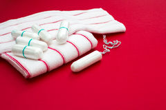 Woman critical days, gynecological menstruation cycle, blood period. Terry bath red towels and menstruation sanitary soft cotton t. Ampons for woman hygiene royalty free stock photos