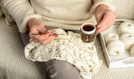 Woman crochet tablecloth. Woman sitting on sofa covered with white woolen blanket, crochet tablecloth and drinking hot black coffee Royalty Free Stock Image