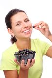 Woman with crockery of currants in her hands. Royalty Free Stock Image