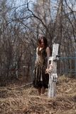 Woman by cross in cemetery. Young woman looking at cross in overgrown cemetery with bare branched trees in background Stock Images