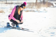 Woman cross country skier putting on ski Stock Images