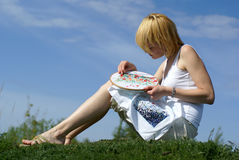 Woman cross-stitching in the park Stock Photos