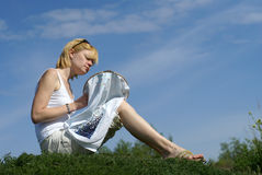 Woman cross-stitching in the park against blue sky Stock Image