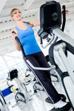 Woman on a cross trainer Stock Photography