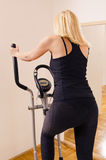 Woman on cross trainer, back view Stock Photos