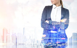 Woman with crossed arms in blue city. Close up of a businesswoman with long blond hair standing with crossed arms against a blue city panorama. Toned image, mock royalty free stock photography