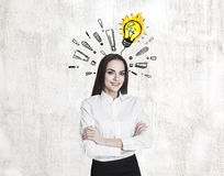 Woman with crossed arms, bulb and exclamations Stock Photos