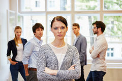 Woman with crossed arms in front of business people Stock Photos