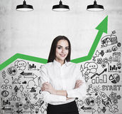 Woman with crossed arms and green graph Royalty Free Stock Image