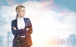 Woman with crossed arms in sunny city. Portrait of a businesswoman with long blond hair standing with crossed arms against a sunny city panorama. Toned image royalty free stock photos