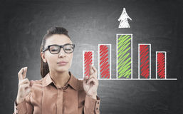 Woman with crossed fingers and bar chart Stock Image
