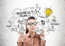 Woman with crossed fingers and business plan. Close up of a businesswoman in a brown blouse and glasses standing with closed eyes and crossed fingers near a Stock Image