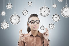Woman with crossed fingers and clocks Stock Photography