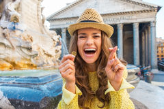 Woman with crossed fingers and coin in rome Stock Images