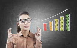 Woman with crossed fingers and graph. Portrait of a young businesswoman in glasses standing with crossed fingers near a blackboard with a growing graph on it Royalty Free Stock Images