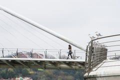 A woman crosses a bridge Royalty Free Stock Images