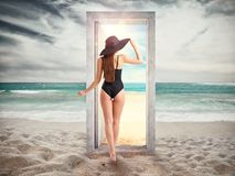 Woman crosses a door on the beach leading to the summer season. royalty free stock photo
