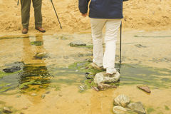 A Woman Crossing a Creek in Scotland, Uk. A woman with white slacks crossing a creek and being met by a man on a beach in Scotland, UK Stock Image