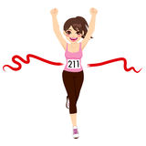 Woman Crossing Finish Line. Beautiful brunette woman crossing red finish line and celebrating victory with fists up Stock Image