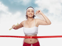 Woman crossing Finishing Line. Portrait of woman holding scroll crossing finishing line Royalty Free Stock Image